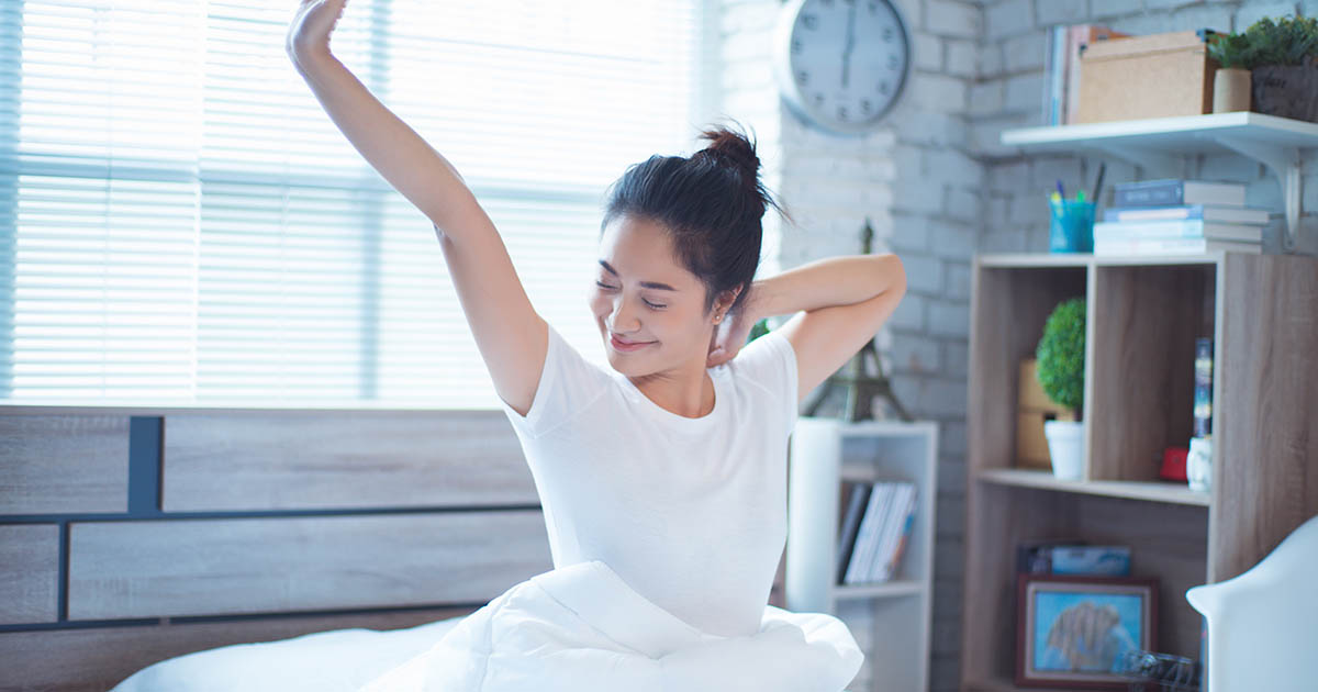 Woman sitting up in bed and stretching