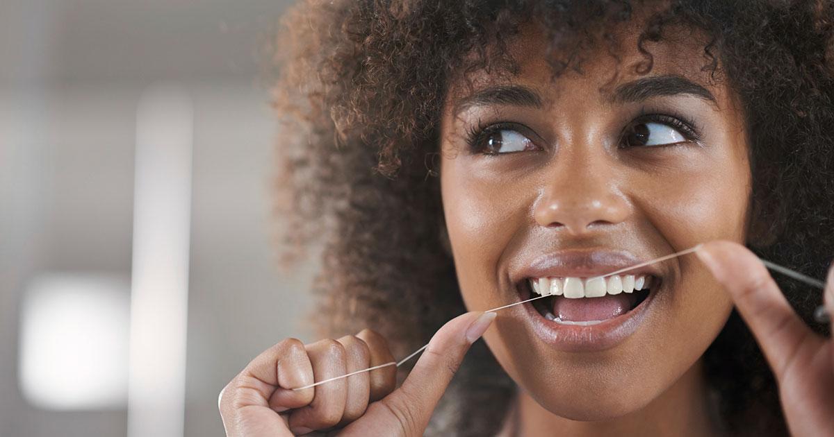 Woman is flossing her teeth