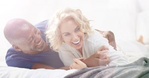 Woman and man lying on stomachs on bed and laughing