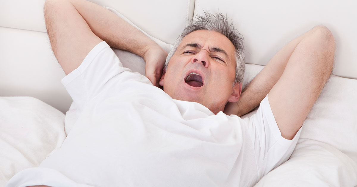 Man yawning with hands behind neck