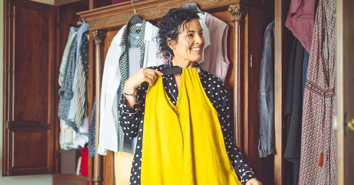 Mature woman deciding on what to wear while holding a yellow dress
