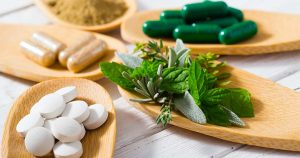 Herbal leaves, ground herb powder and medicament pills on bamboo spoons