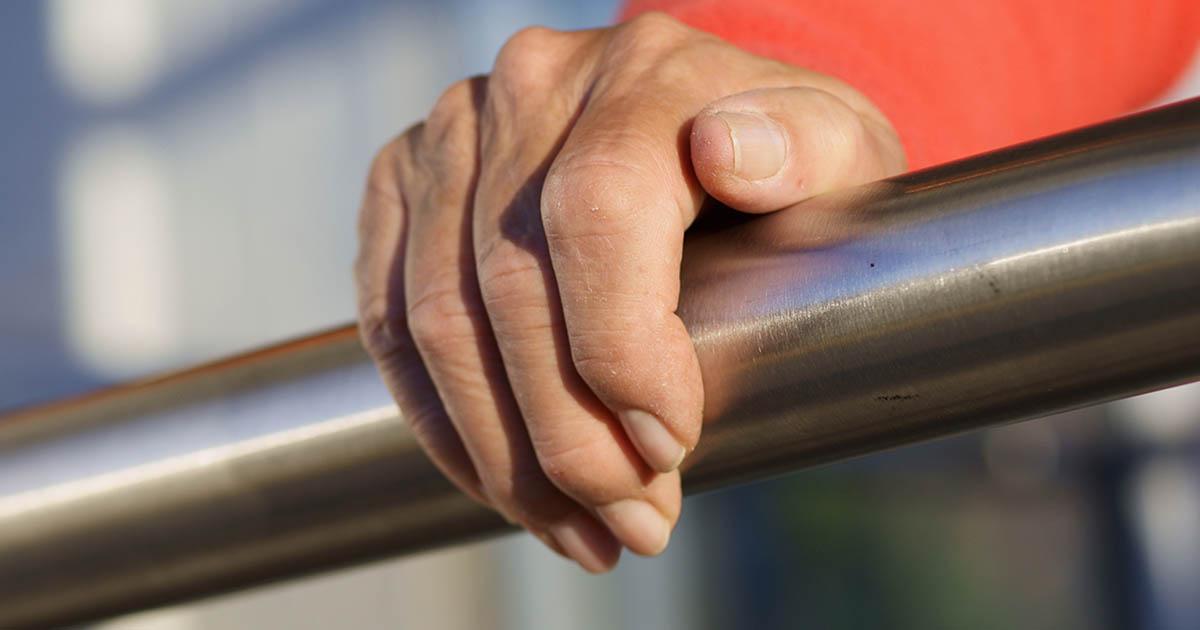 Closeup of hand gripping railing
