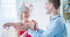 Physical therapist is helping a mature female patient stretch