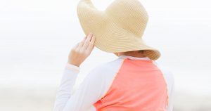 A woman is outside wearing a hat and a long-sleeve shirt