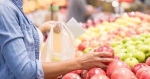 Woman picks out pomegranate in supermarket