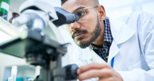 Scientist looking in microscope while working on medical research in science laboratory