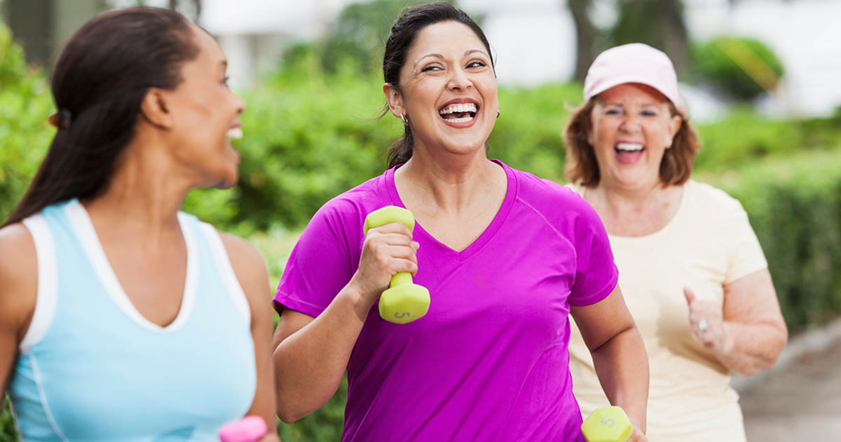 A group of woman are outdoors power-walking with weights in hands