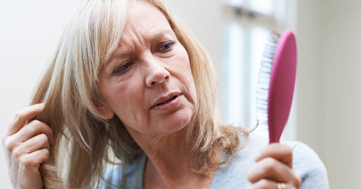 Mature woman with brush is concerned about hair loss