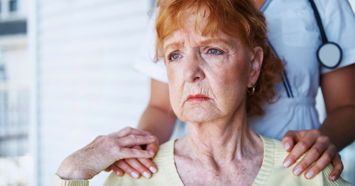Older woman looking concerned with nurse's hands resting on shoulders