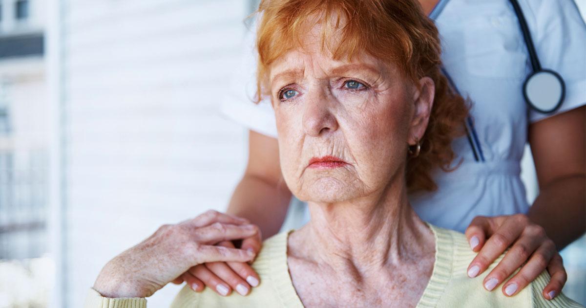 Older woman looking concerned with nurse's hands resting on shoulders