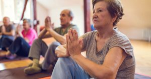 Older people sitting on yoga mats with hands pressed together
