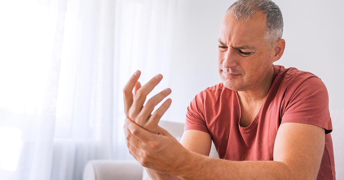 Mature man suffering from wrist and hand pain at home while sitting on sofa during the day