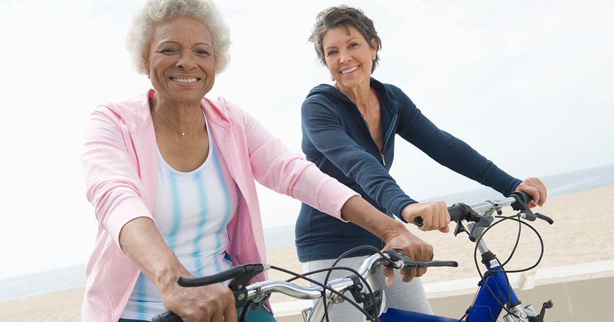 Two mature women biking outside by the beach