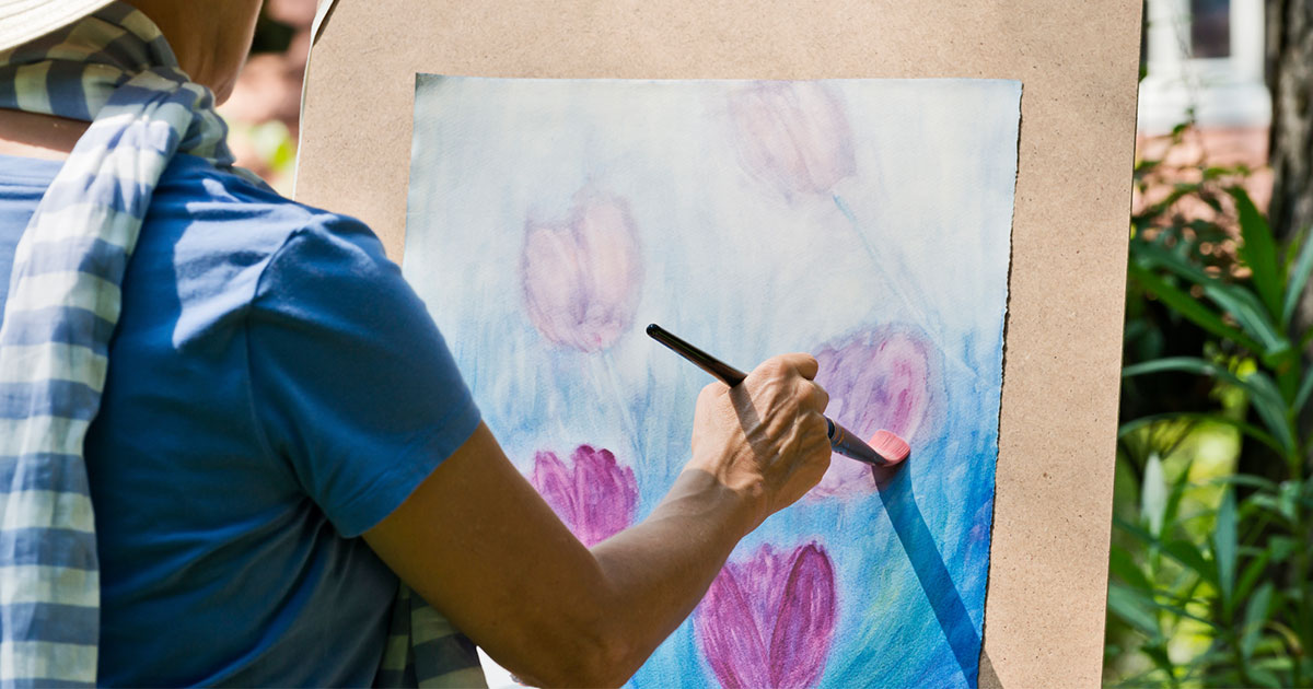A woman is painting flowers outside