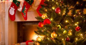 Decorated Christmas tree in front of a fireplace with stockings