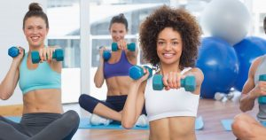 Woman sitting on yoga mats holding free weights
