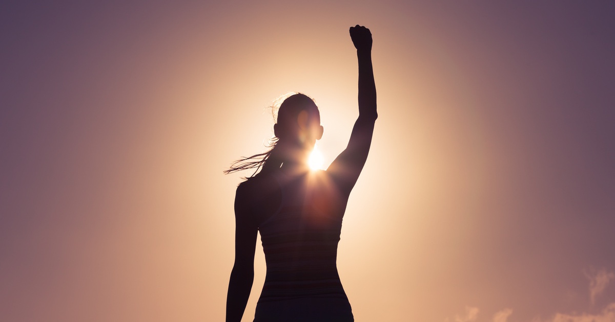 Silhouette of a woman with her arm raised