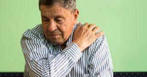 Older man holding his shoulder