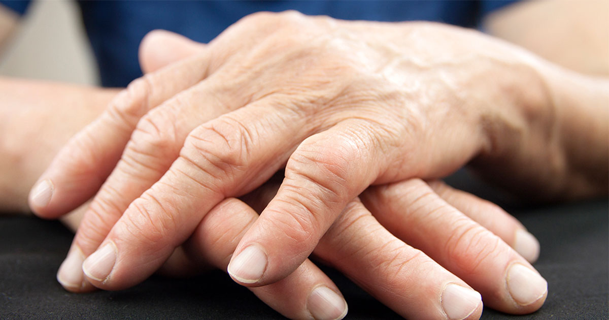 Older person's hands folded on a table