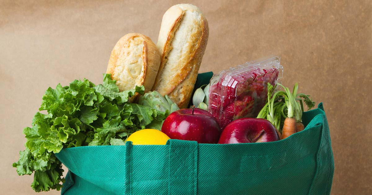 Burlap bag of produce and loaves of bread