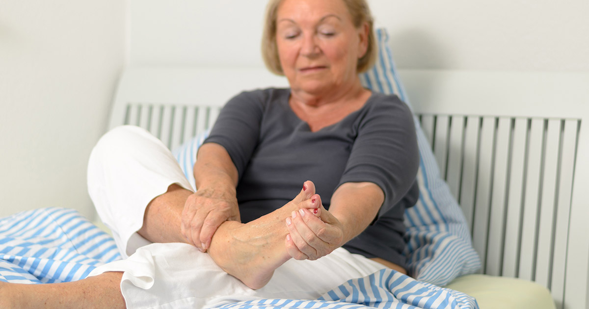 Older woman holding her ankle and foot