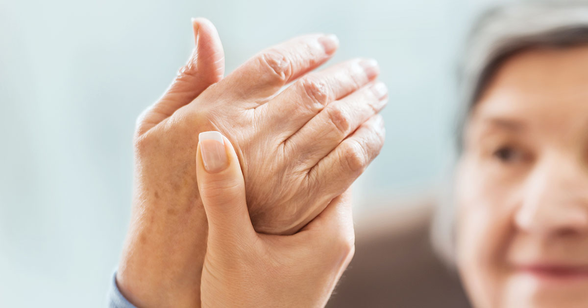 Older woman's hand being held by a professional