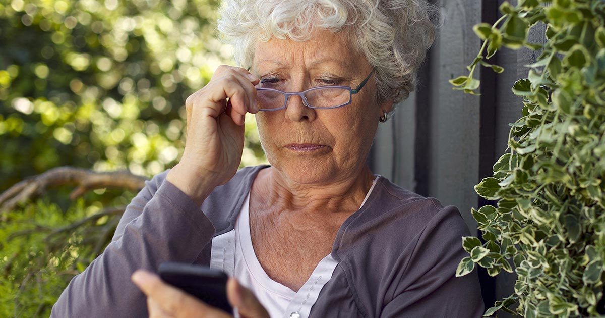 Older woman with one hand on her glasses and the other holding a phone