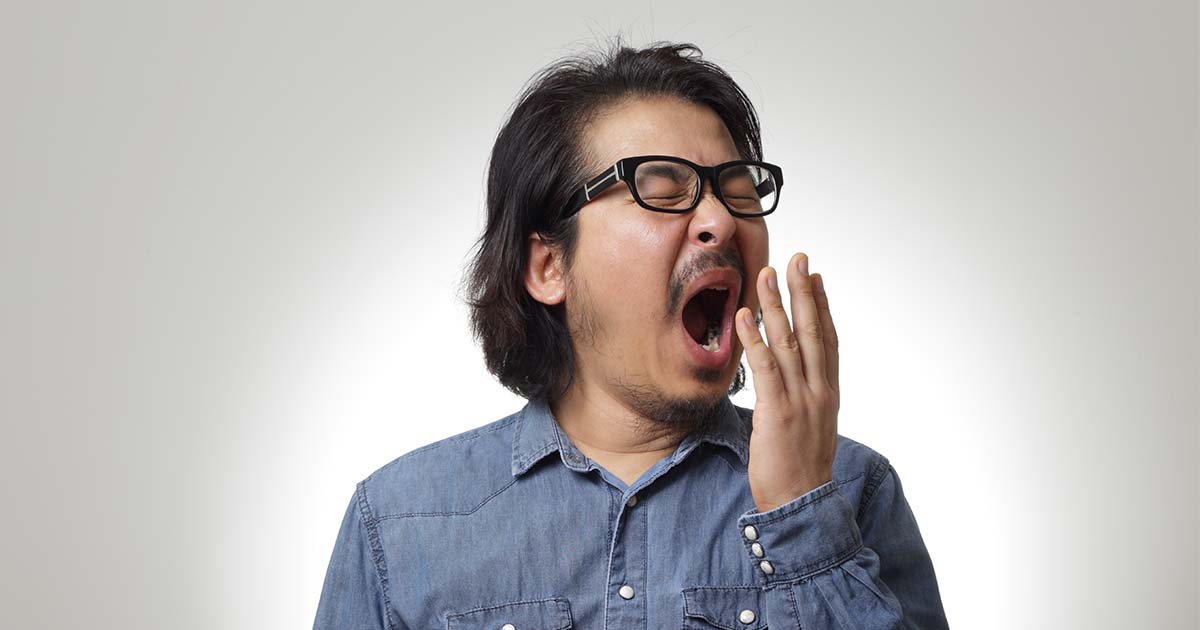Man yawning with hand hovering in front of mouth