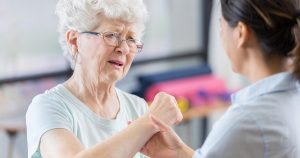 Older woman looking pained as another woman holds her wrist
