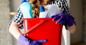 Woman wearing latex gloves and holding a bucket of cleaning supplies