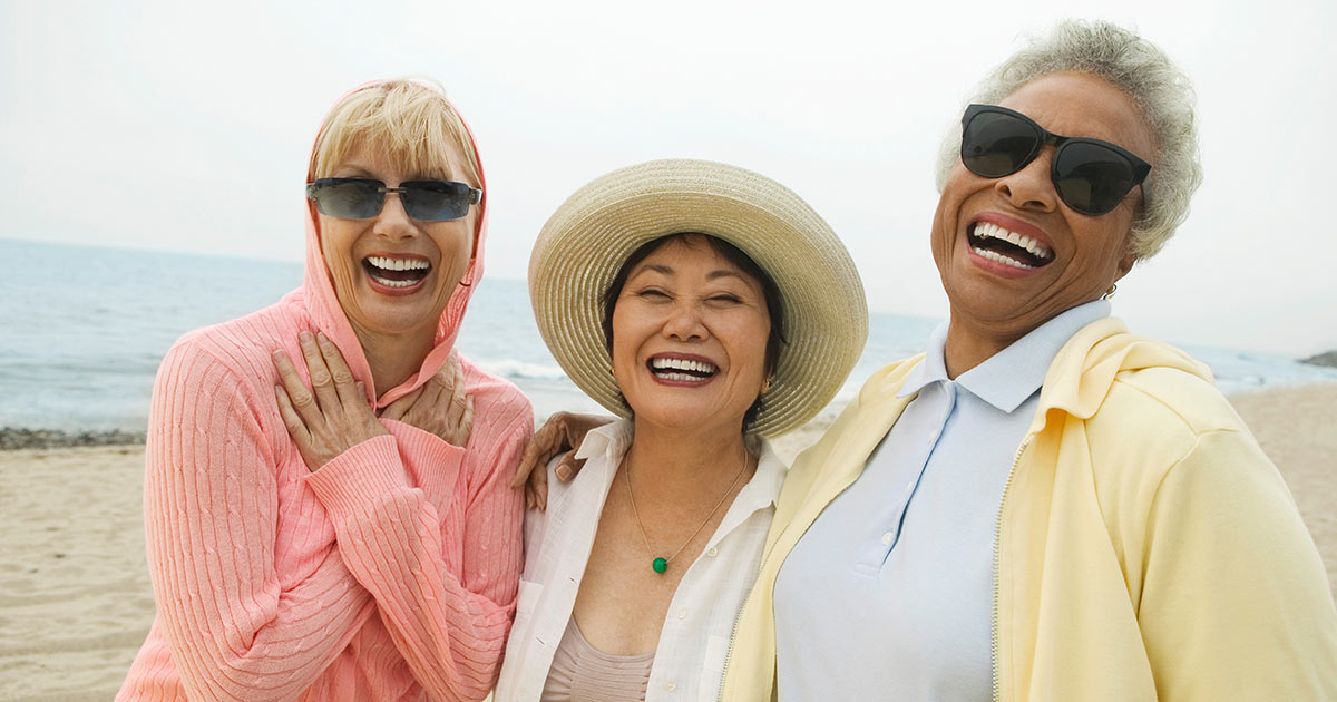Three older woman standing arm in arm, laughing on the beach