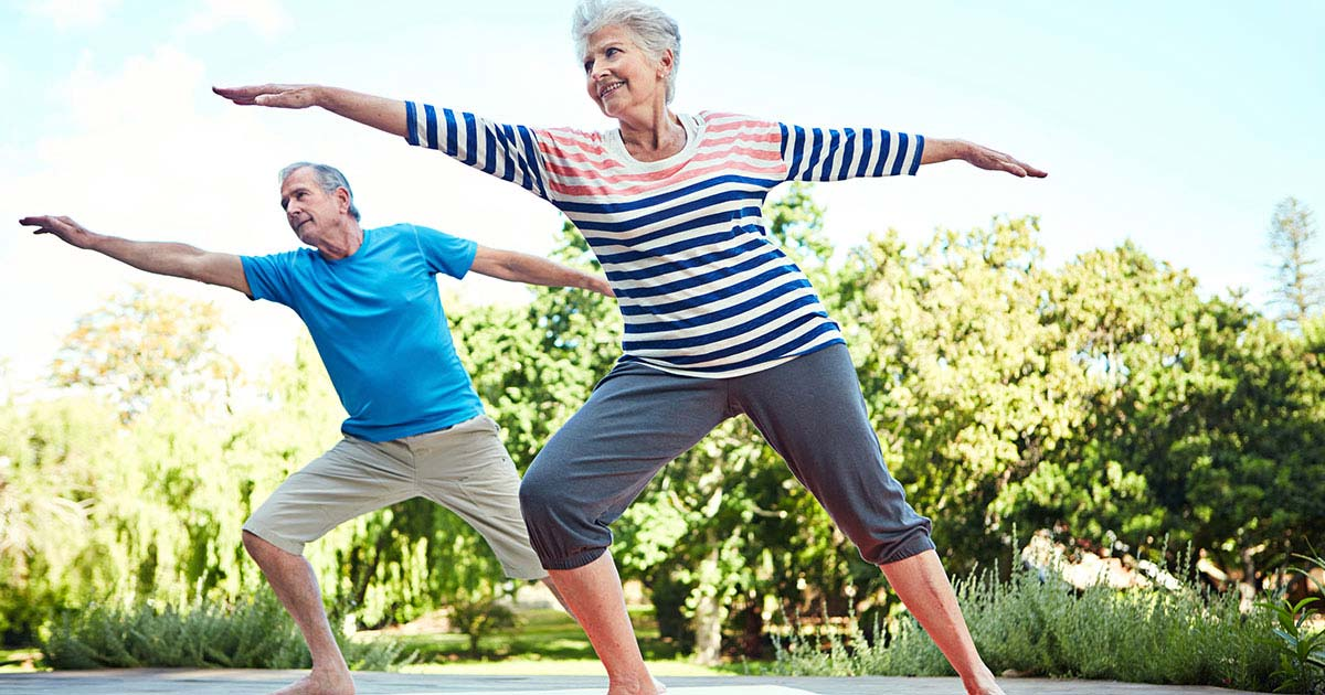 Older woman and man doing yoga outside