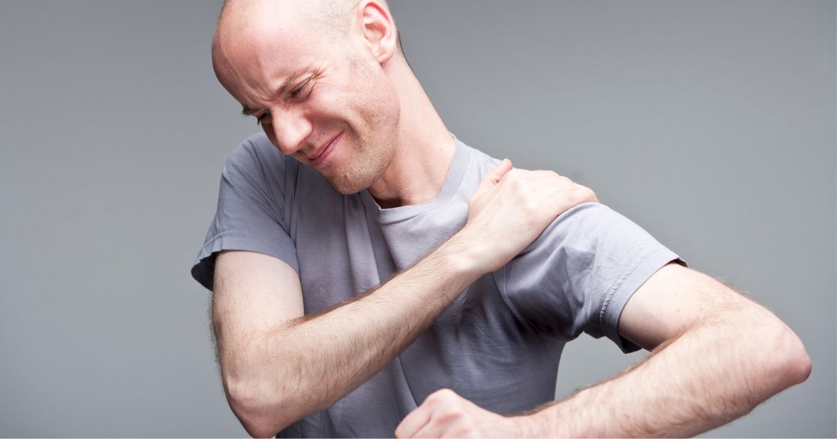 a man experiencing pain in his spine, neck and shoulders; this is a symptoms of ankylosing spondylitis