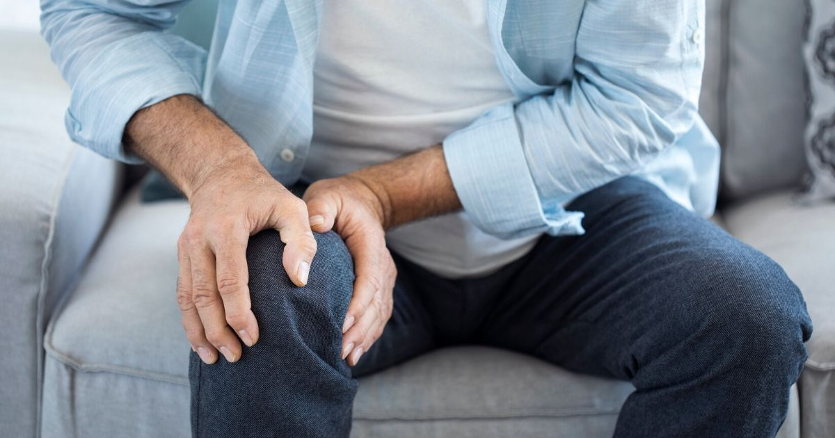 a man with arthritis pain sitting down and holding his knee