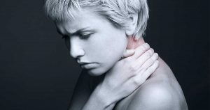 a woman experiencing shoulder and neck pain, one of the symptoms of polymyalgia rheumatica