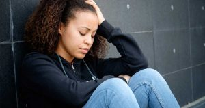 a woman sitting down looking sad and frustrated, showing signs of emotional stress