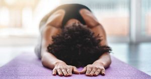 a woman doing yoga on a mat: a great example of exercise for rheumatoid arthritis