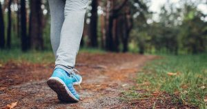 A person's legs, with blue running shoes on, walking on a trail in a forest.