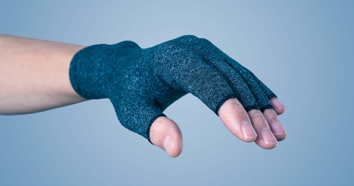 Someone wearing a navy blue compression glove with exposed fingertips.