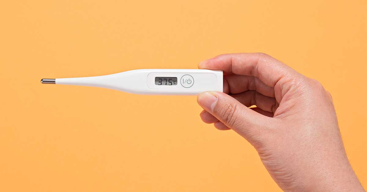 A person holding a thermometer in front of an orange background.